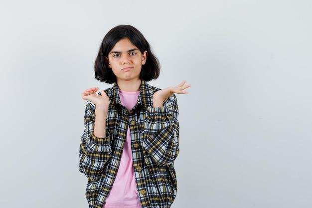 Preteen meisje toont ik weet geen gebaar in shirt, jas vooraanzicht.