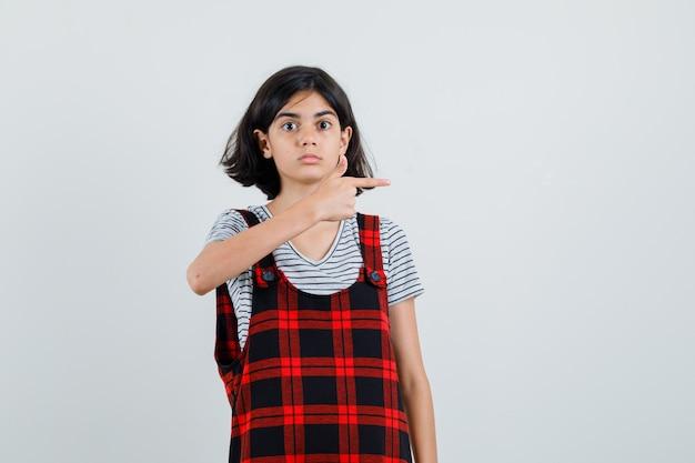 Preteen meisje wijst naar links in t-shirt, jumpsuit en kijkt voorzichtig