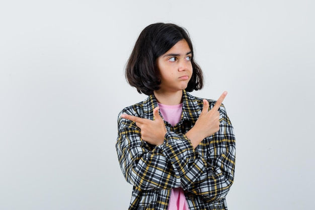 Preteen meisje wijzend naar verschillende kanten in shirt, jas, vooraanzicht.
