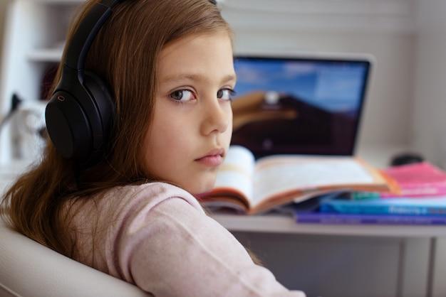 Preteen schoolmeisje doet haar huiswerk met laptopcomputer thuis. kind dat gadgets gebruikt om te studeren. online onderwijs en afstandsonderwijs voor kinderen. thuisonderwijs tijdens quarantaine.