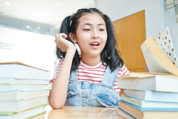 Preteen vietnamees meisje dat veel boeken op haar bureau bekijkt