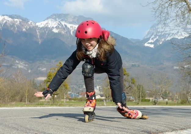 Preteen vrij meisje op rolschaatsen in helm bij een spoor