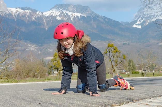 Preteen vrij meisje op rolschaatsen in helm