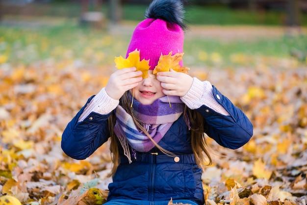 Preteen vrouwelijk kind spelen met gebladerte in herfst park