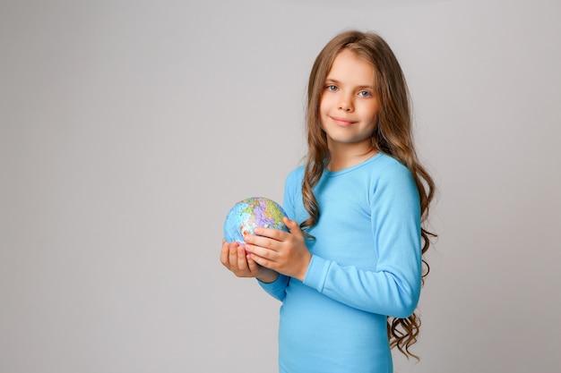 Preteenmeisje dat een aardebol houdt