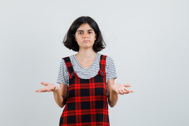 Preteenmeisje dat hulpeloos gebaar in t-shirt, jumpsuit toont en ontevreden kijkt