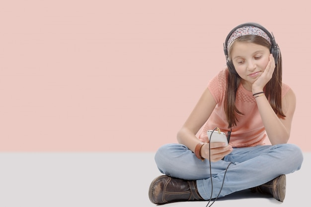 Preteenmeisje die met zijn smartphone naar muziek luisteren, die in kleermakerszit zit