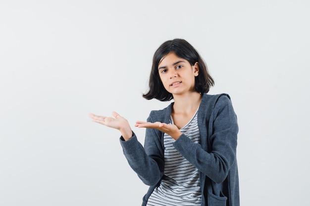 Preteenmeisje in overhemd, jasje dat opzij wijst en gefocust kijkt