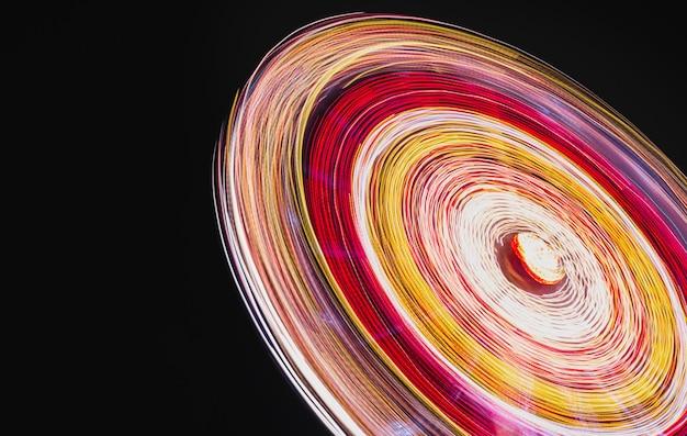 Pretpark carrousel neonlichtenlange blootstelling oranje licht draaiende attractiereuzenrad l