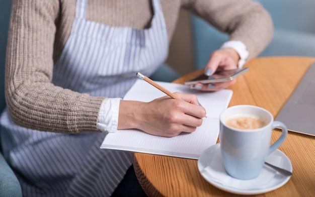 Prettig werk. jonge mooie vrouw maken van aantekeningen en het gebruik van mobiele telefoon zittend bij de tafel.