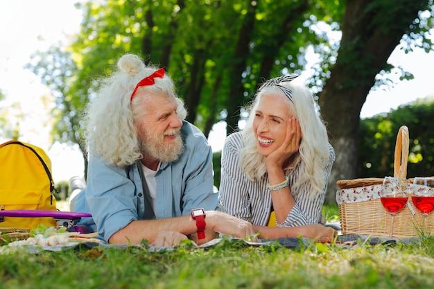 Prettige communicatie. vrolijk opgetogen paar met elkaar praten terwijl ze op het gras liggen