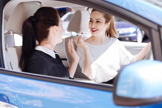 Prettige interactie. gelukkig positieve mooie vrouw zit achter het stuur en houdt een lippenstift vast terwijl ze met haar vriend praat