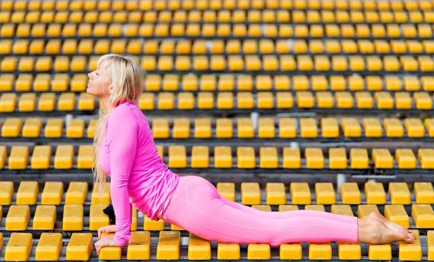 Prettige jonge vrouw die roze sportkleding draagt die yoga-asana's in het park doet op zonnige dag op gele achtergrond