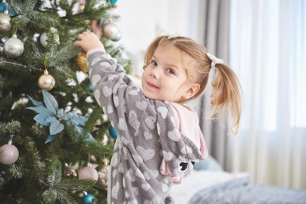 Prettige kerstdagen en een fijne vakantie! jong meisje dat het verfraaien van de kerstboom helpt, die sommige kerstmissnuisterijen in haar hand houdt