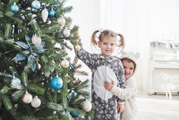 Prettige kerstdagen en een fijne vakantie! jonge meisjes helpen bij het versieren van de kerstboom, met wat kerstballen in haar hand