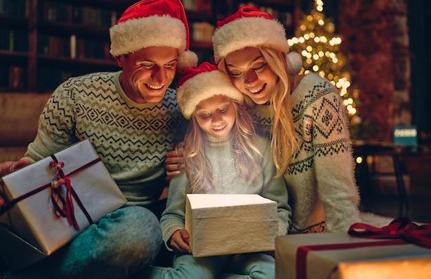 Prettige kerstdagen en een gelukkig nieuwjaar! gelukkige familie wacht op het nieuwe jaar in kerstman hoeden. ouders presenteren geschenkdoos aan hun charmante dochter. magisch licht van binnenuit.