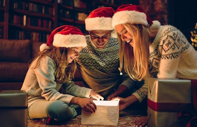 Prettige kerstdagen en een gelukkig nieuwjaar! gelukkige familie wacht op het nieuwe jaar in kerstman hoeden. ouders presenteren geschenkdoos aan hun charmante dochter.