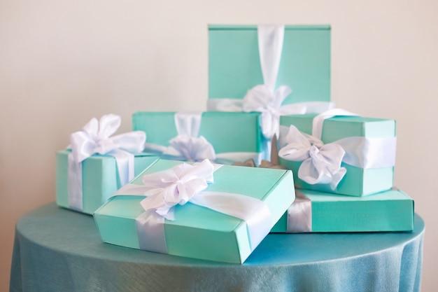 Prettige kerstdagen en een gelukkig nieuwjaarsvakantie! vroege morgen. blauwe dozen met geschenken met witte linten staan op de tafel.