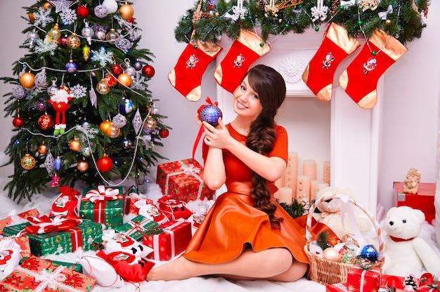 Prettige kerstdagen en een gelukkig nieuwjaarsvakantie! vrolijke schattige jonge vrouw met cadeautjes. het mooie meisje houdt binnen een bal voor kerstmisdecoratie dichtbij kerstboom