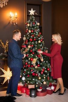 Prettige kerstdagen en fijne feestdagen. familie, man en vrouw versieren kerstboom