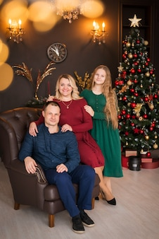 Prettige kerstdagen en fijne feestdagen. gelukkig gezin in een mooie kamer in de buurt van de kerstboom