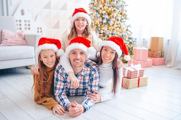 Prettige kerstdagen en fijne feestdagen. gezin van vier met kerstmis thuis