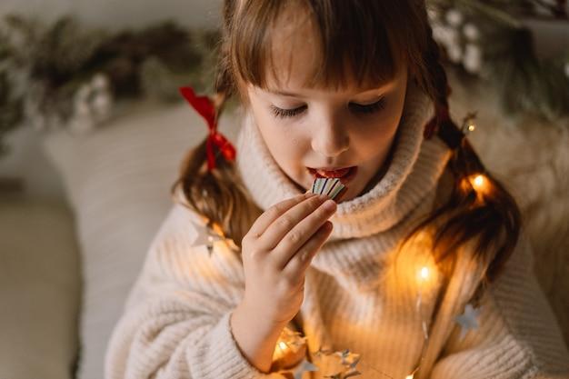 Prettige kerstdagen en fijne feestdagen. het kind dat peperkoekkoekjes eet. wachten op kerstmis.