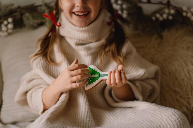 Prettige kerstdagen en fijne feestdagen. het kind speelt met peperkoekkoekjes. wachten op kerstmis.