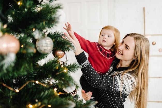 Prettige kerstdagen en fijne feestdagen moeder en dochter versieren de kerstboom thuis