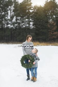 Prettige kerstdagen en fijne feestdagen. moeder en haar zoontje lopen samen in winter woud