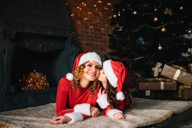 Prettige kerstdagen en fijne feestdagen! mooie moeder met dochtertje in kerstkostuums brengen samen tijd door in de buurt van de kerstboom.