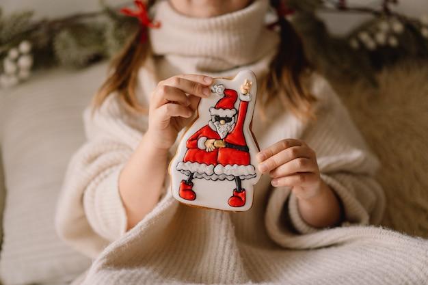 Prettige kerstdagen en fijne feestdagen. peperkoekkoekjes in de hand van een kind. wachten op kerstmis.