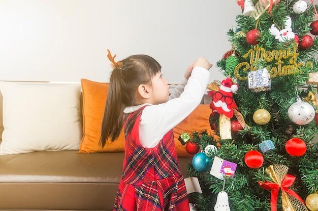 Prettige kerstdagen en fijne feestdagen! vakantie en jeugd concept. gelukkig klein glimlachend meisje met de doos van de kerstmisgift.