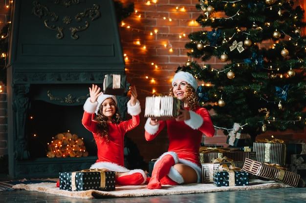 Prettige kerstdagen en fijne feestdagen! vrolijke moeder en haar schattige dochtermeisje in kerstkostuums die geschenken uitwisselen.