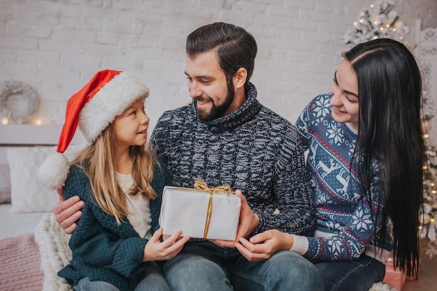 Prettige kerstdagen en fijne feestdagen vrolijke moeder, vader en haar schattige dochtermeisje wisselen geschenken uit.