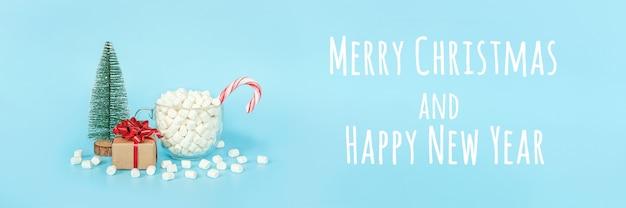 Prettige kerstdagen en gelukkig nieuwjaar briefkaart. geschenkdoos, kerstboom en kopje marshmallows met rode lollystok op blauwe achtergrond. vakantieconcept. vooraanzicht, spandoek.