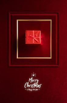 Prettige kerstdagen en gelukkig nieuwjaar gloeien met rode kerstcadeau in fotolijst op fluwelen rode vilt stoffen muur.