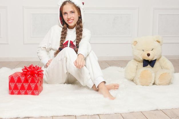 Prettige kerstdagen en gelukkig nieuwjaar mooi gelukkig kind meisje in pyjama wachten op een wonder thuis met kerstboom. weinig glimlachend meisje met de doos van de kerstmisgift. vakantie en mensen concept.