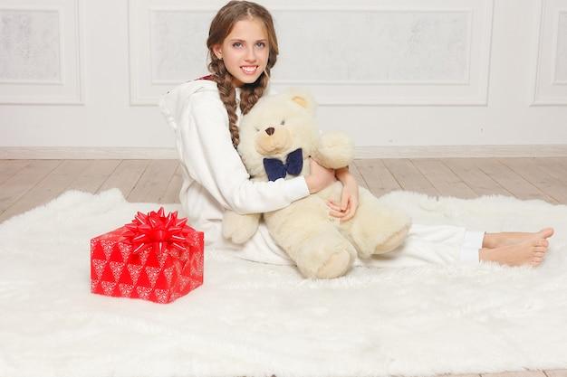Prettige kerstdagen en gelukkig nieuwjaar mooi gelukkig kind meisje in pyjama wachten op een wonder thuis met kerstboom