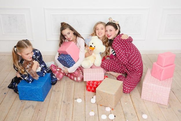 Prettige kerstdagen en gelukkig nieuwjaar mooi gelukkig vier kind meisje in pyjama wachten op een wonder thuis met kerstboom. klein lachend meisje met de doos van de gift van kerstmis. vakantie, mensenconcept.