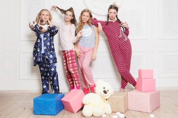 Prettige kerstdagen en gelukkig nieuwjaar mooi gelukkig vier kind meisje in pyjama wachten op een wonder thuis met kerstboom. weinig glimlachend meisje met de doos van de kerstmisgift. vakantie, mensen concept.