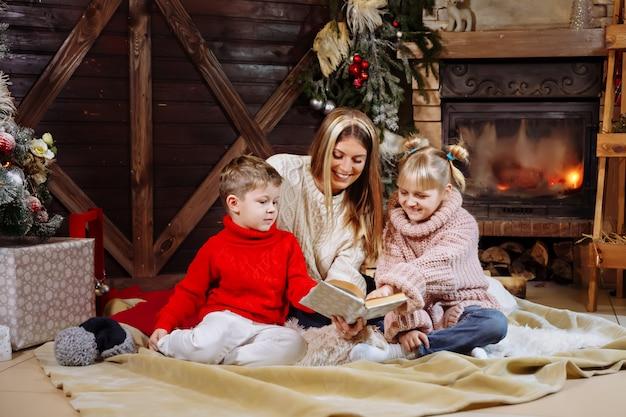Prettige kerstdagen en gelukkig nieuwjaar, mooie jonge moeder lezen van een boek aan haar dochter en zoon in de buurt van de kerstboom.