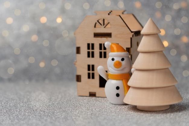 Prettige kerstdagen en gelukkig nieuwjaar samenstelling. kleine sneeuwman, huisje en boom