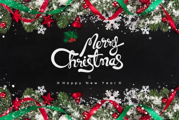 Prettige kerstdagen en gelukkig nieuwjaar tekst met decoratieve ornamenten op blackboard