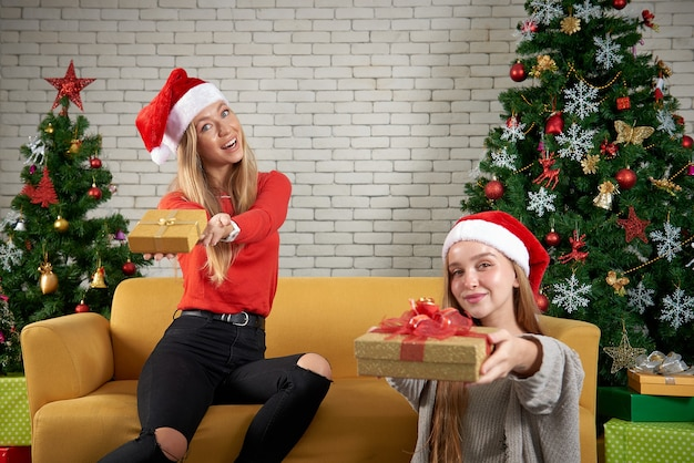 Prettige kerstdagen en gelukkig nieuwjaar vakantie, mooie witte kaukasische vrouw vieren, geschenken uitwisselen ontspannen voor een gele bank en kerstboom op kamer