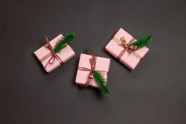 Prettige kerstdagen en gelukkig nieuwjaar wenskaart. kerstcadeau dozen decoratief ambachtelijk papier en vuur op donker zwart. winter xmas vakantiethema. plat leggen.