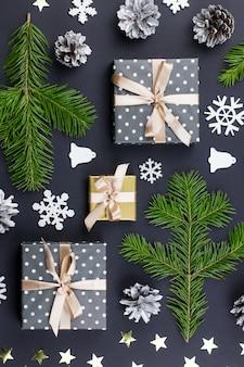 Prettige kerstdagen en gelukkig nieuwjaar wenskaart met dennentakken, cadeautjes, decoraties op zwart