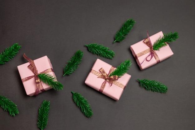 Prettige kerstdagen en gelukkig nieuwjaar wenskaart of banner. kerst ambachtelijke papier roze geschenkdozen met vuren tak op donker zwart