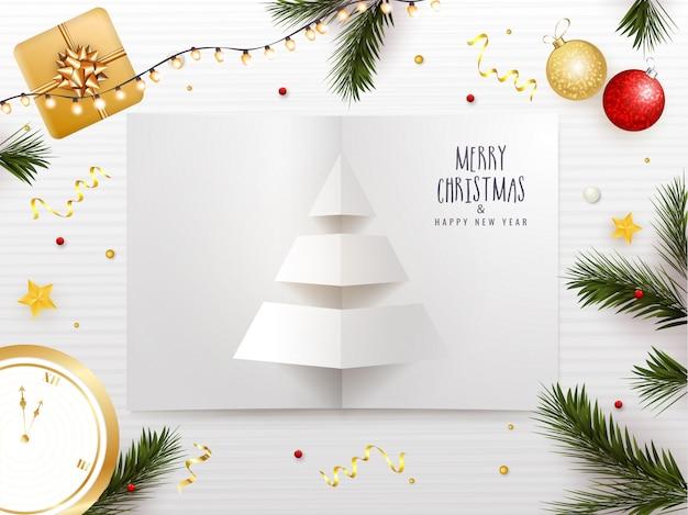 Prettige kerstdagen en gelukkig nieuwjaar wenskaartontwerp met papier gesneden kerstboom, kerstballen, geschenkdoos, klok en pijnboombladeren versierd op wit gestreept