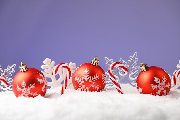 Prettige kerstdagen en gelukkig nieuwjaarskaart met rode ballen sneeuwvlokken en snoep